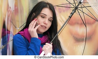 European girl talking on the smartphone under the umbrella