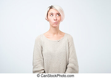 European girl with dyed hair looking away, having doubtful and indecisive face expression, pursuing her lips