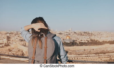 European girl with grey backpack enjoys Jerusalem. Female tourist looks at ancient old town in Israel from a skydeck. 4K