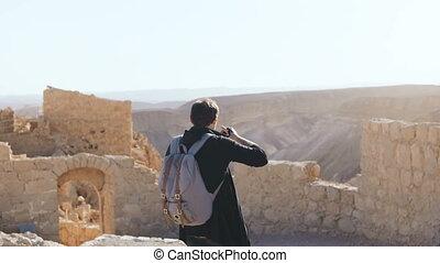 European man takes photos of ancient scenery. Male tourist...