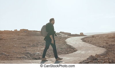 European man walks to ancient ruins, looks around. Relaxed...