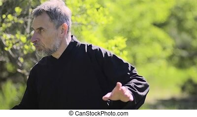 European master taijiquan demonstrates kung fu with a fighting stick