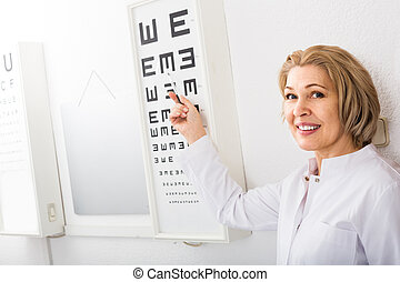 female optician standing near eye chart and smiling - ...