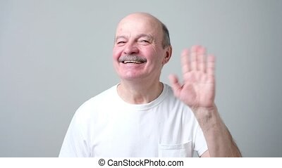European pensioner waives hand in hello gesture while...