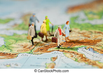 European Tourism And Travel, a group of miniature model tourists with luggage on a map of Europe, shallow DOF