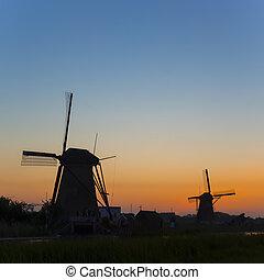 European Travel Destinations. Line of Traditional Romantic Dutch Windmills in Kinderdijk Village in the Netherlands During Golden Hour.