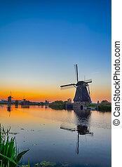 European Travel Destinations. Traditional Romantic Dutch Windmills in Kinderdijk Village in the Netherlands During Golden Hour.