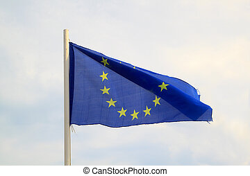 European Union flag on a blue sky with clouds background