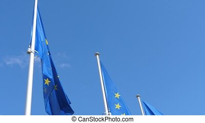 European Union flags, signs of unity, waving in celeste sky in slow motion