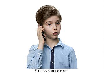 European white boy in blue shirt talking on smartphone on white background.