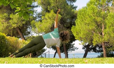 European woman doing yoga and relaxation exercises outdoors....