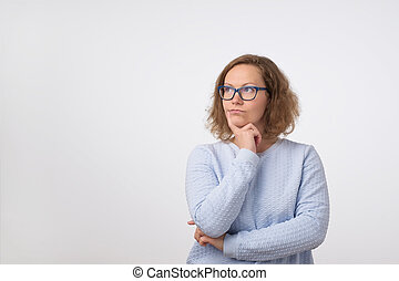 European woman in glasses looking up on empty place and thinking. She is making plan for day.