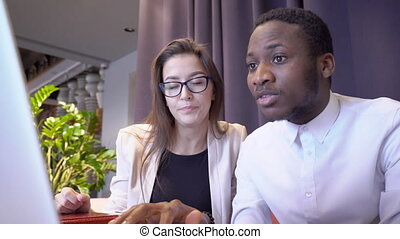 European woman shows African American man interesting information on monitor.
