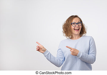 European woman swith smile showing product. Beautiful girl with curly hair pointing to the side