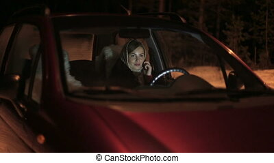 European woman talking with mobile phone while sitting in car on driver seat