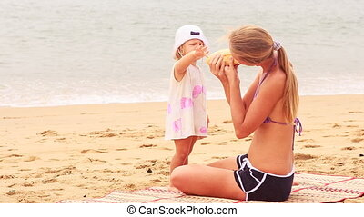 blonde mother and little daughter sit on mat and bite off roll