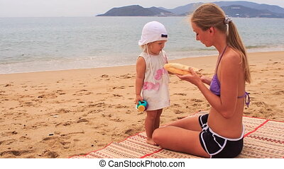blonde mother and little daughter sit on mat and eat roll