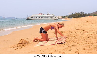 young blonde woman cleans mat from sand on beach