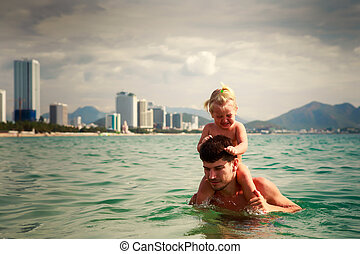 father carries little daughter on shoulders in sea water