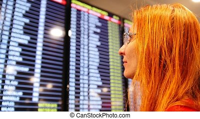 European young red hair woman looking at timetable departure board on airport