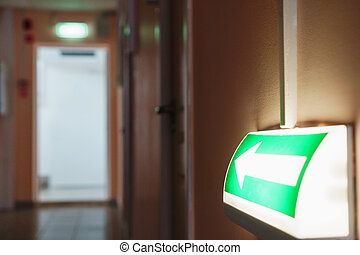 Evacuation arrow with illumination from the building to the room, guiding to the exit.