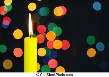 Eve - Flame of candle and garland lights out of focus in the...