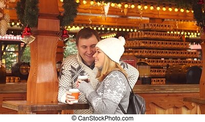 Eve of Christmas. Cute young couple has good time at the Christmas bazaar.