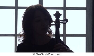 Evening against the window girl plays the cello . Close up . Silhouette