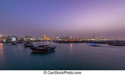 Evening at Doha Bay day to night timelapse with Traditional Wooden Dhow Fishing Boats.