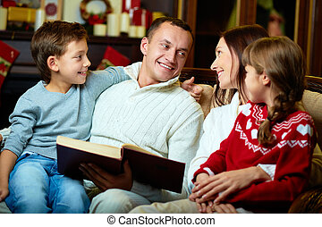 Evening at home - Portrait of friendly family reading book...