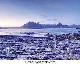 Evening at Loch Scavaig with Cuillins mountains in warm...