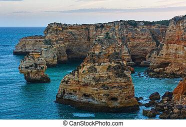 Evening Atlantic rocky coastline near Lagoa, in Algarve, Portugal.