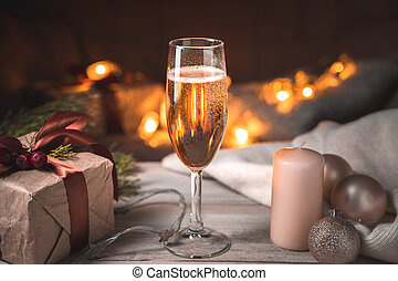 Evening Christmas background with a full glass of champagne on the background of a burning garland.