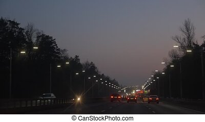 Evening city road lighting view from driving car