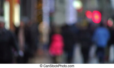 Evening city street with pedestrians and blurred lights