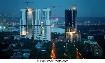Evening cityscape of construction site among houses, cars...
