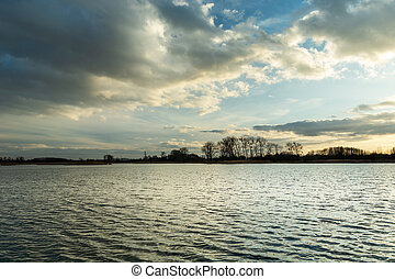 Evening clouds in the sky over a peaceful lake