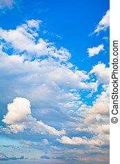 evening cumulus clouds in blue summer sky
