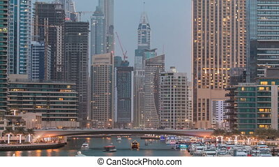 Evening Dubai marina city centre with floating vessels day to night timelapse