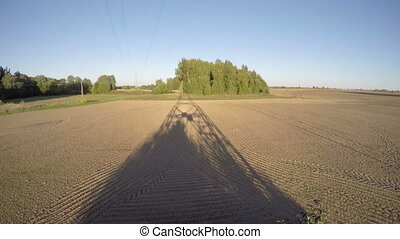 evening electric tower shadow on plowed field. Time lapse 4K...