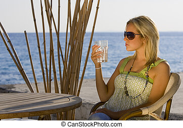 Evening Glow - A beautiful young blond woman on a beach...