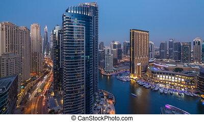 Evening illumination of Dubai Marina day to night aerial...