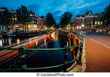 Evening in Amsterdam city, light trails and reflections on water at the Leidsegracht and Keizersgracht canals. Long exposure shot. City trip visiting concept