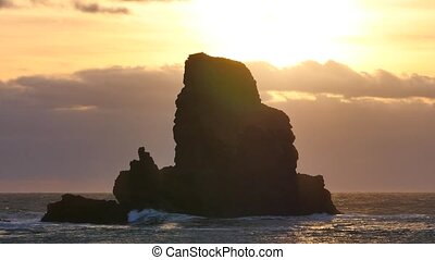 Evening in Talisker bay on west coast of the Isle of Skye in Scotland during an windy sunset. Sharp rocky tower above foamy sea of the Hebrides, waves crashing against to boulders and sharp rock