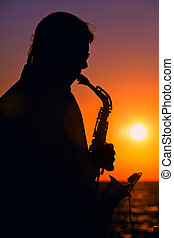 Evening Jazz - Man playing on saxophone on sunset