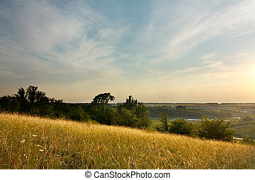 Evening Landscape with cirrus clouds and magical light of the sunset over rural expanses
