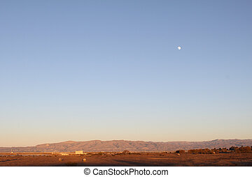 Evening landscape with mountains on the horizon and the Moon