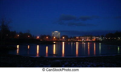 Evening lights of Petrozavodsk on river shore