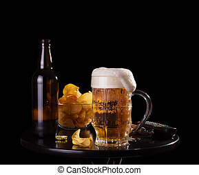Evening male guests. Beer with foam in the glass, crisp chips, watching TV isolated on black