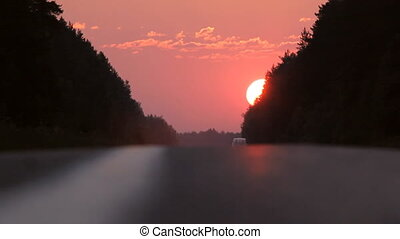 Evening road with car on sunset background